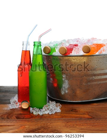 A metal party bucket on a wooden table full of cold soda pop. Two bottles on the table with drinking straws. - stock photo