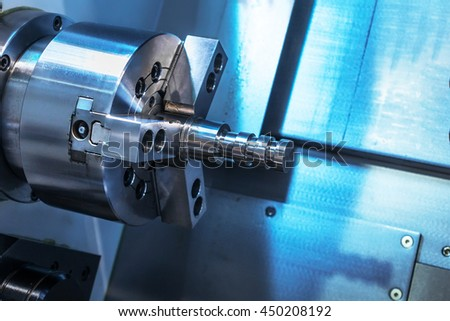 A metal workpiece clamped in the lathe chuck CNC machine. Shallow depth of field. - stock photo
