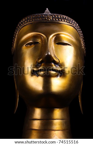 A metallic idol of a Buddha idol, on black studio background.