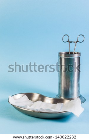 a metallic surgical tray with gauze and a cylindric container with surgical forceps inside