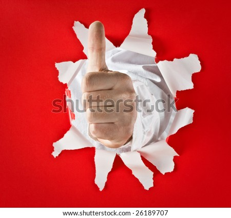 A metaphorical image of a male hand with a 'thumbs up' gesture wishing luck, coming through a hole in a red paper. - stock photo