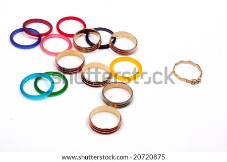 A metaphorical picture of a unique golden ring standing out from a group of colorful rings, on a white background. This image depicts leadership or uniqueness.