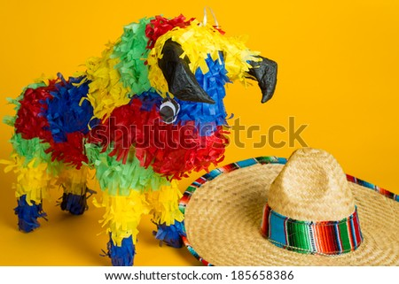A mexican torro pinata and sombrero on a yellow background - stock photo