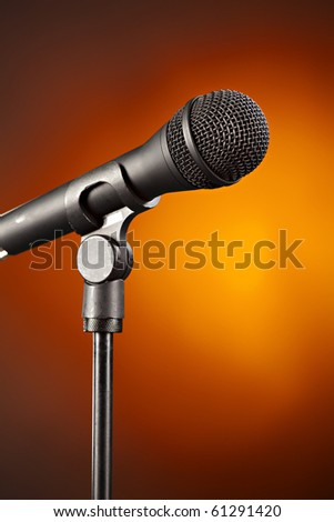 A microphone on a stand isolated against a spotlight gold background.