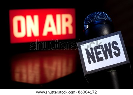 A Microphone with the word News on the side and on-air radio and television broadcast sign in the background with copy space.