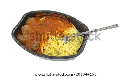 A microwaved spaghetti and meatball TV dinner in a black tray with a fork inserted into the pasta on a white background. - stock photo