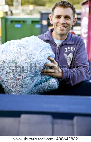 A mid-adult man recycling a bag of shredded paper - stock photo