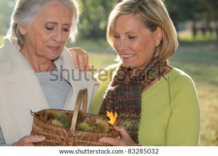 a mid age blonde woman and an older woman holding a wickerwork basket full of chestnuts - stock photo