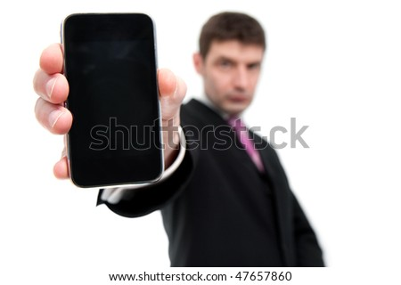 A mid thirties businessman in a black suit holds a smart phone in his hand close to the camera.  Differential focus on the phone