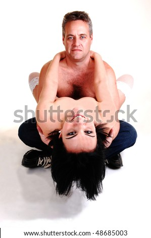 A middle age couple, she topless in red panties lying on the floor with nice black hair and the man holding her legs on his lap, looking at her. - stock photo