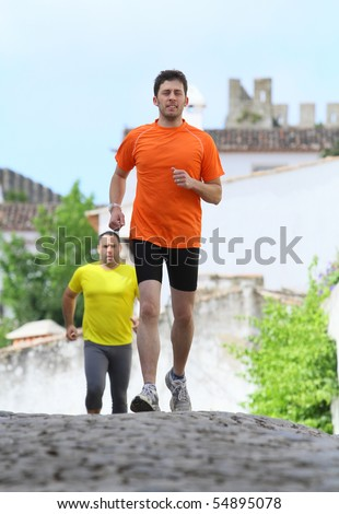 A middle age man running full of energy on a town road - stock photo