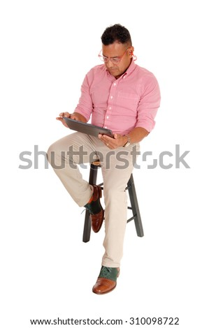 A middle age man sitting on a chair with safety glasses and earplug's working