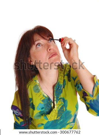 A middle age woman in a colorful dress looking up and putting makeup