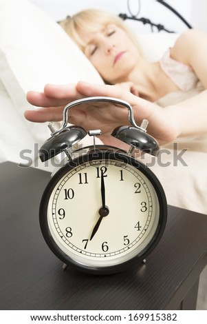 A middle age woman reached for alarm clock in foreground which reads seven o'clock.