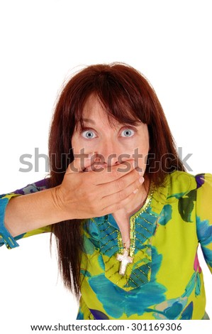 A middle age women in a colorful dress is shocked, with her hand over her