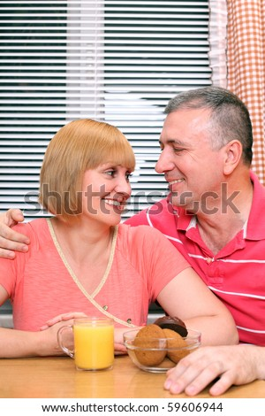 A middle aged couple looking at each other with love before having meal - stock photo