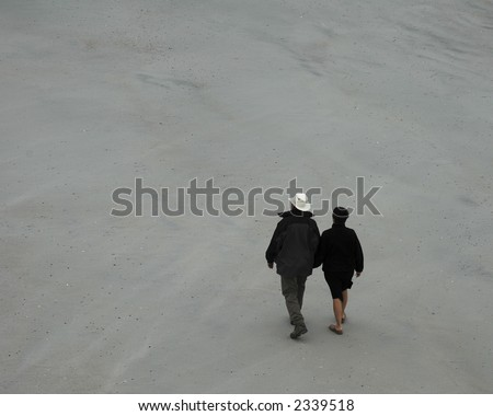 A middle-aged couple strolling on an empty beach on a chilly, overcast day.