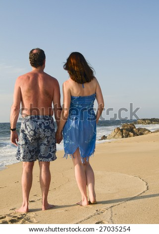 A middle aged couple walks the beach holding hands.