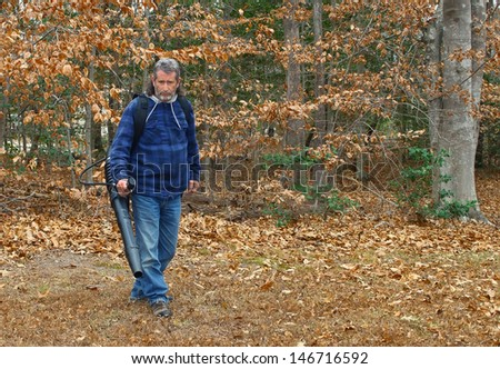 A middle aged long gray haired white male outside working on a fall day blowing leaves out in the yard - stock photo