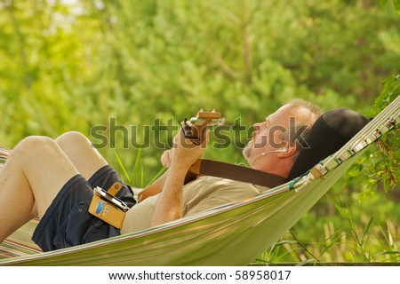 A middle aged man composing music with a guitar and hand held recording device in a hammock in the shade in the summer. - stock photo