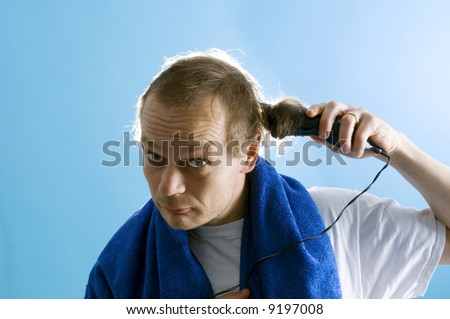 A middle aged man dressed in a white t-shirt, shaving his own hair with a clipper - stock photo