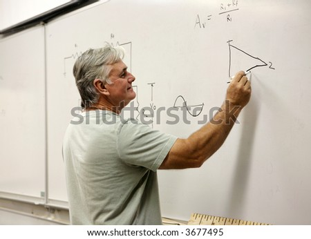 A middle aged man going back to school, or a teacher writing on the board. - stock photo