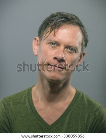 a middle aged man in a green t shirt smiles casualy at the camera - stock photo