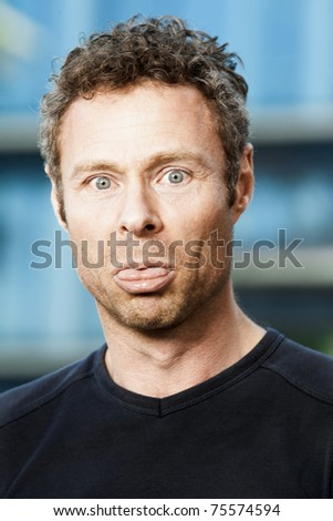 A middle aged man sticking his tongue out in fun - stock photo
