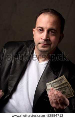 A middle aged man wearing a leather jacket holding a handful of one hundred dollar bills. Shallow depth of field.