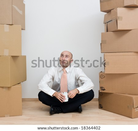 A middle-aged man with a coffee cup sitting in between stacked cardboard boxes containing his belongings, after shifting in a new house. - stock photo
