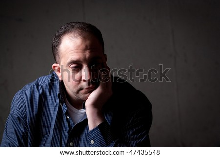 A middle aged man with a contemplative look on his face.  He could be worried or depressed about something. - stock photo