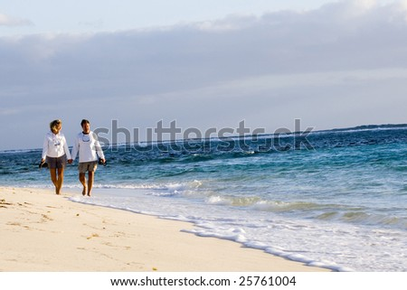 A middle-aged retired man and woman walk down a deserted beach in the Bahamas.