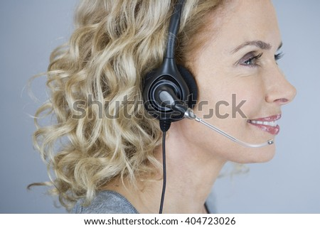A middle aged woman wearing a headset - stock photo