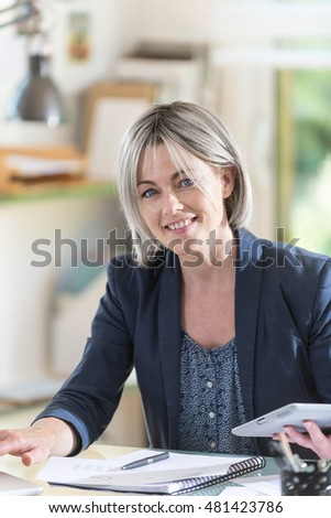 a middle-aged woman with gray hair who works in an office with a tablet and a PC. she is a businesswoman. her face is smiling. she looks at the camera with confidence and determination