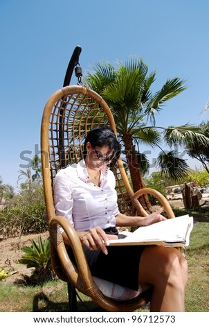A middle eastern female reading a book in a garden - stock photo
