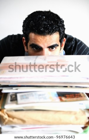 A middle eastern man behind piles of files and papers