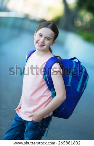 A middle school child in a pink shirt with a purple backpack