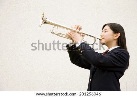 A middle school girl playing the trumpet