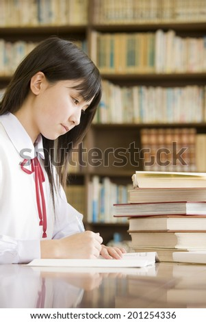 A middle school girl studying in a library