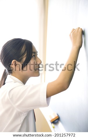 A middle school girl writing an answer on a blackboard
