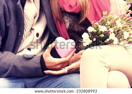 A midsection of a romantic couple sitting on a bench in the park holding Valentines gift and flowers - stock photo