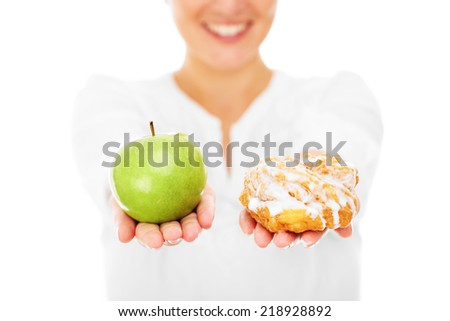 A midsection of a woman showing an apple and a donut over white background - stock photo
