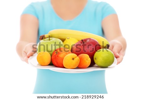 A midsection of a woman with a plate of fruits over white background