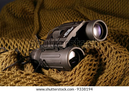A military black spyglass laid on a camouflage mimetic green scarf - stock photo