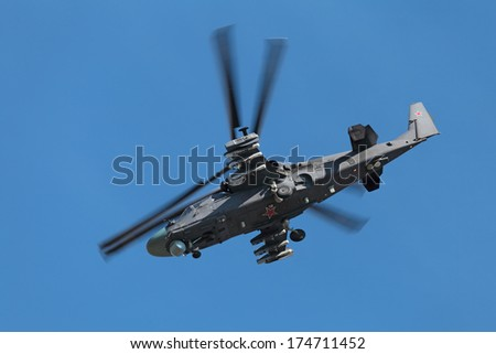 A military helicopter flying on the background of blue sky