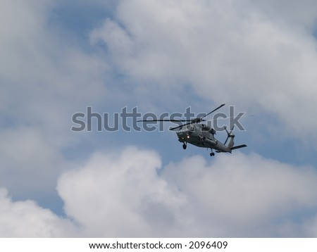 A military helicopter hovering in a cloudy sky