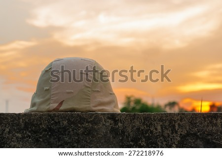 A military helmet of desert camouflage  with gray sunset background - stock photo