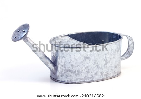 A miniature metal watering can, isolated on a white background. - stock photo
