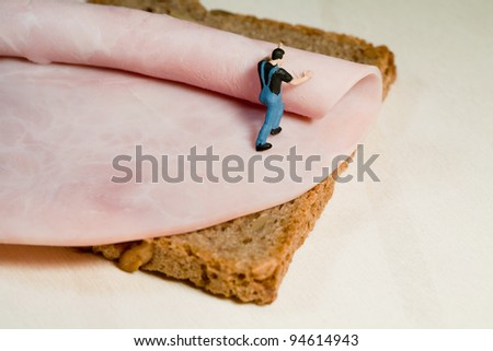 A miniature model workman rolls out a slice of ham on a slice of brown bread, back view with copyspace. - stock photo