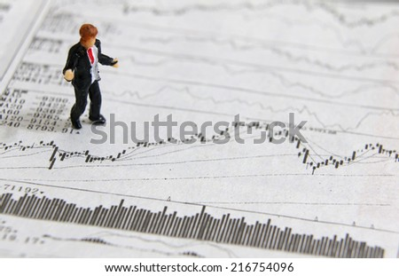 A miniature people reading financial charts